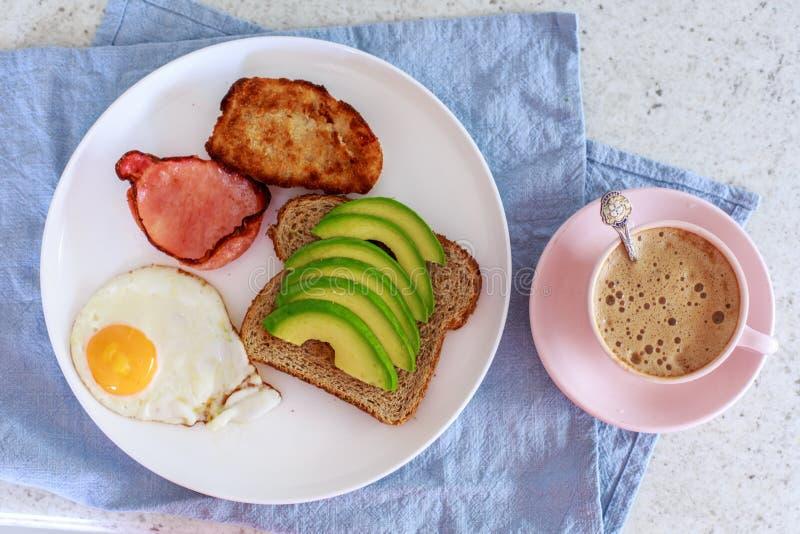 英式早餐、鲕梨、鸡蛋、多士、烟肉和香肠 免版税库存图片