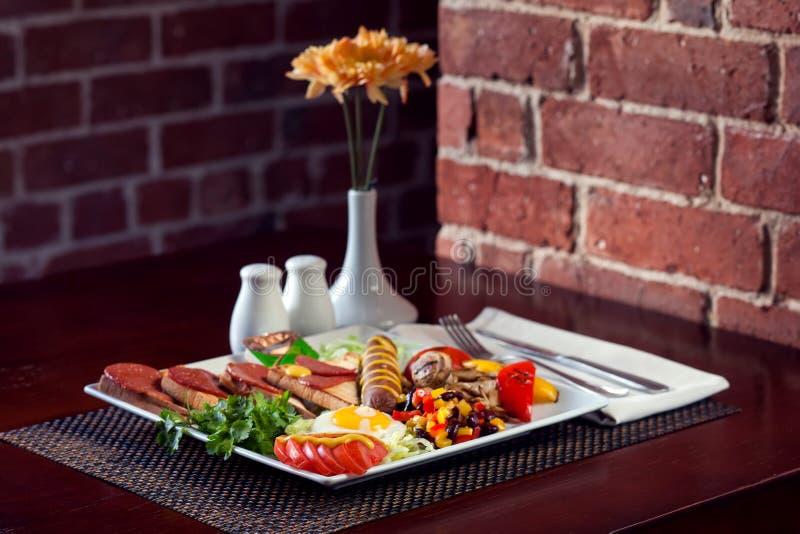 英式早餐包括香肠、烤蕃茄和蘑菇、鸡蛋、烟肉、被烘烤的豆和面包 食物和餐馆 免版税图库摄影