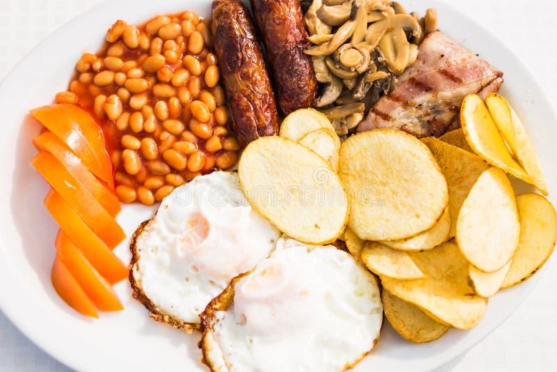 英式早餐包括香肠、蕃茄和蘑菇,鸡蛋,烟肉,烘烤了豆和芯片 免版税库存图片