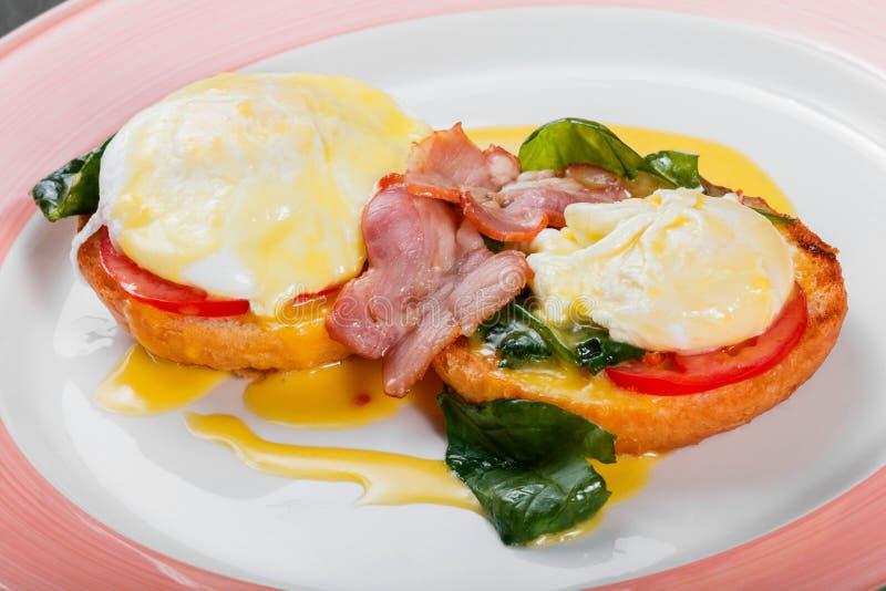 英式早餐炸面包多士用鸡蛋、菠菜、蕃茄、无盐干酪乳酪和火腿在板材 免版税库存图片