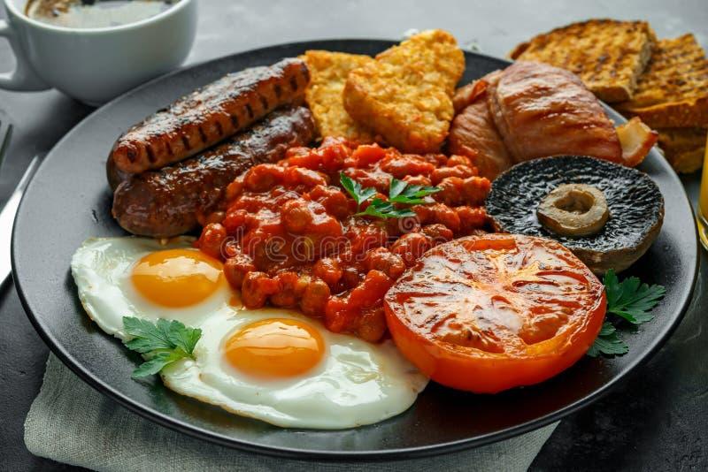 英式早餐用烟肉、香肠、煎蛋、被烘烤的豆、马铃薯煎饼和蘑菇在黑色的盘子 托起咖啡 库存图片