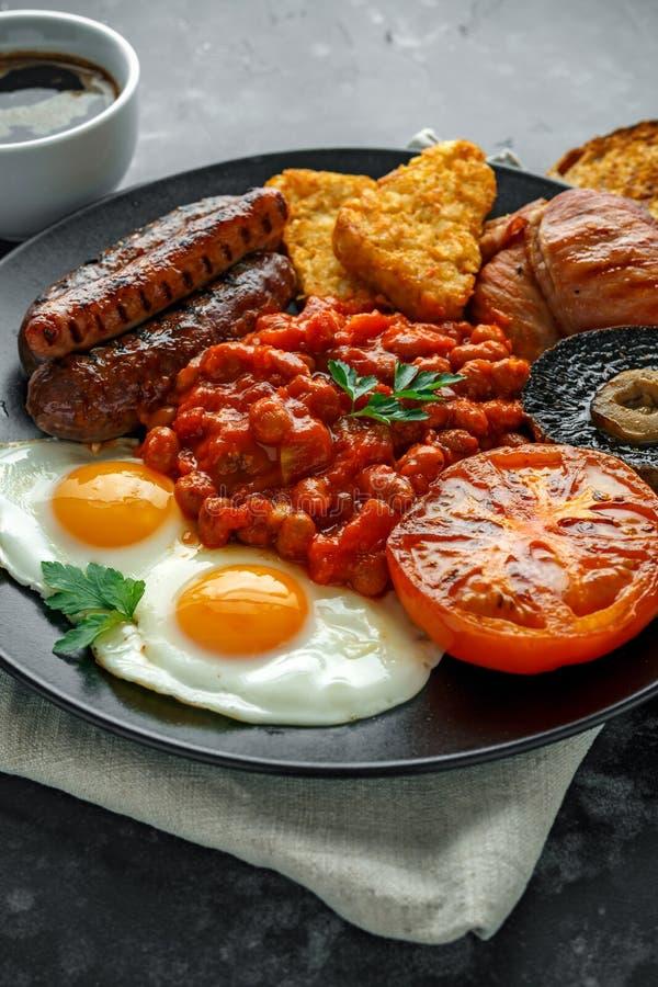 英式早餐用烟肉、香肠、煎蛋、被烘烤的豆、马铃薯煎饼和蘑菇在黑色的盘子 托起咖啡 免版税图库摄影