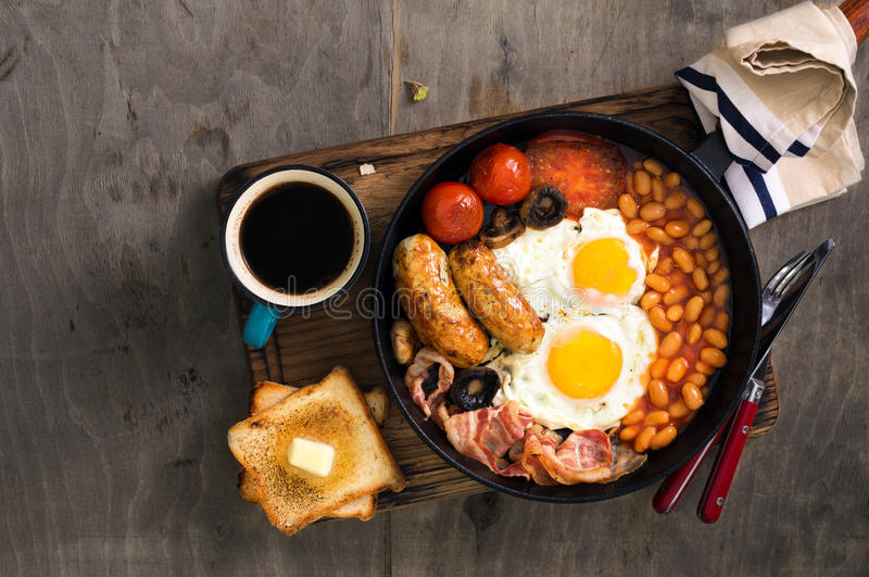 英式早餐用香肠,烟肉,煎蛋,豆,多士 图库摄影