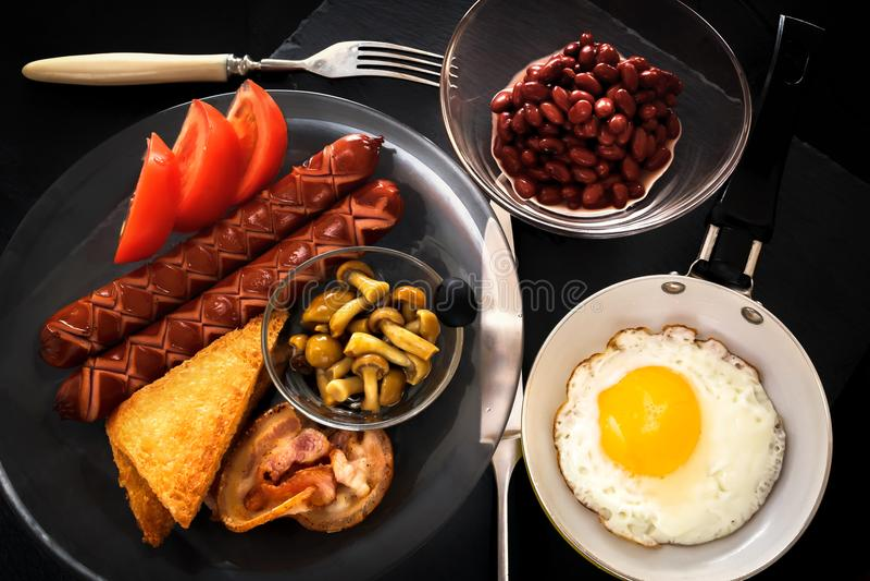 英式早餐用鸡蛋、烟肉、香肠、多士、豆、蘑菇、蕃茄和汁液 鸡蛋油煎的煎锅 库存图片