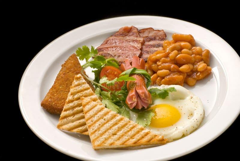英式早餐:荷包蛋、烟肉、豆和多士在板材 免版税图库摄影