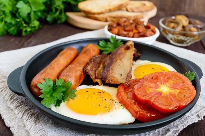 英式早餐:香肠,烟肉,蕃茄,鸡蛋,在调味汁的豆,油煎了蘑菇,多士 免版税库存图片