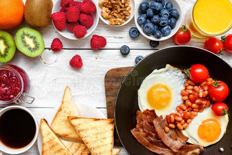 英式早餐-煎蛋、豆、蕃茄、咖啡、烟肉和多士用新鲜水果和莓果 免版税图库摄影
