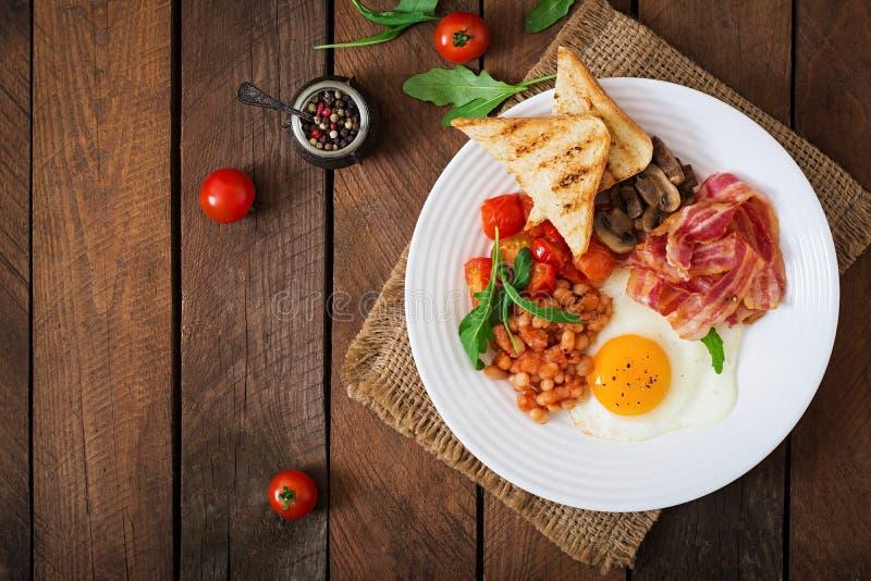 英式早餐-煎蛋、豆、蕃茄、蘑菇、烟肉和多士 库存照片