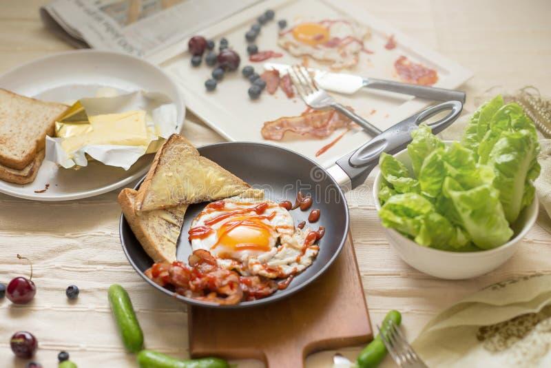 英式早餐-煎蛋,烟肉,面包蓝莓 免版税图库摄影
