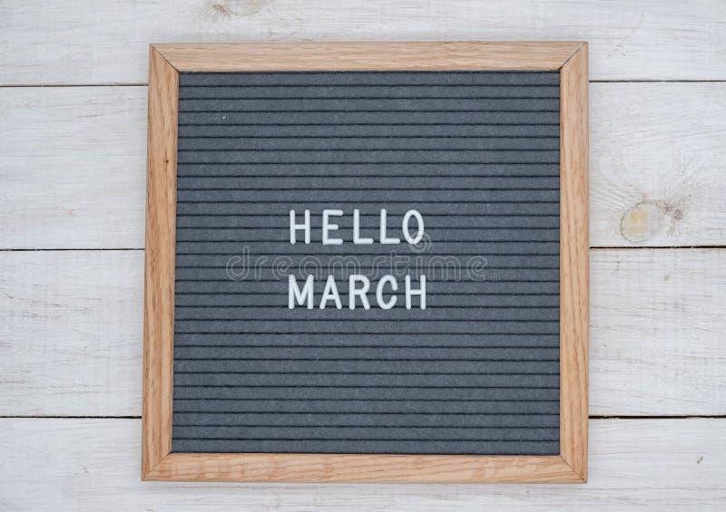 英语发短信给你好在一个信件板的3月在灰色背景的白色信件 免版税库存图片