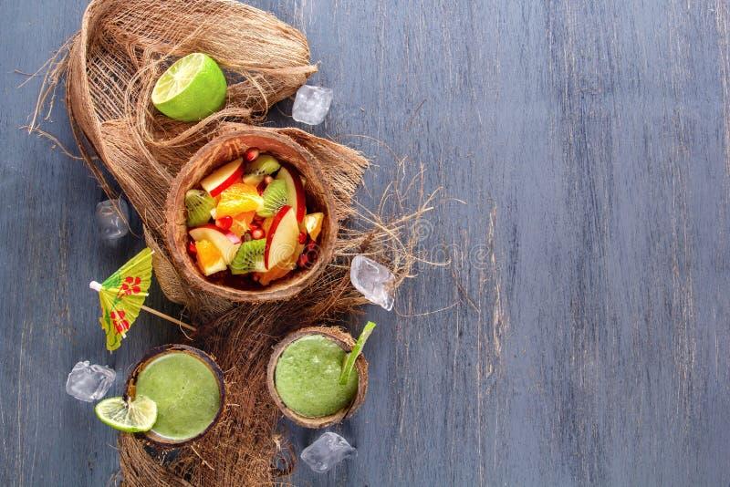 苹果、猕猴桃、桔子和石榴水果沙拉在一半椰子与冰和新鲜的绿色圆滑的人与石灰和薄菏 免版税库存照片