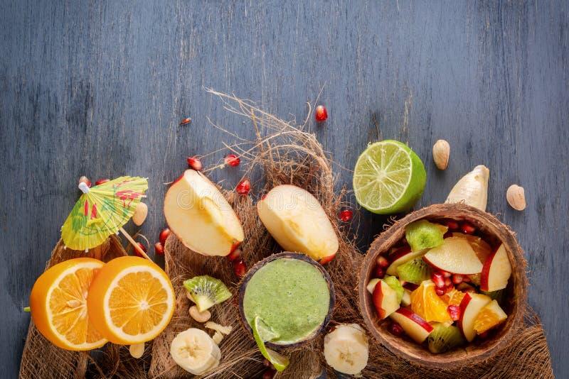 苹果、香蕉、桔子和石榴在一半椰子和新鲜的绿色圆滑的人水果沙拉从菜、石灰和薄菏 库存照片