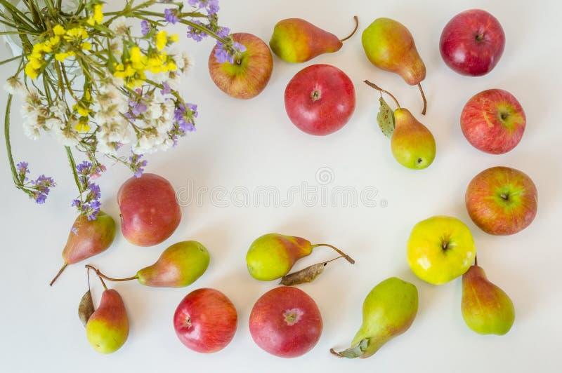 苹果和梨长方形框架在白色桌上 免版税库存图片