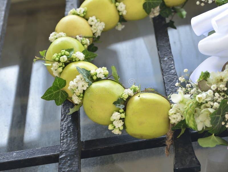 苹果常春藤和白花绿色花圈在门 库存图片