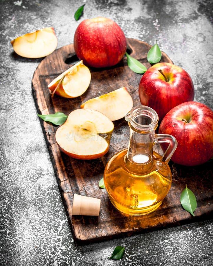 苹果汁醋用在切板的新鲜的苹果 库存照片