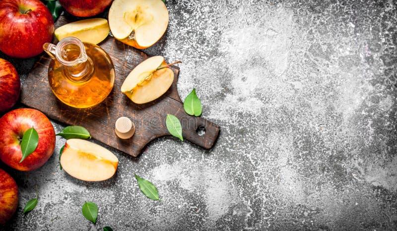 苹果汁醋用在切板的新鲜的苹果 免版税库存图片