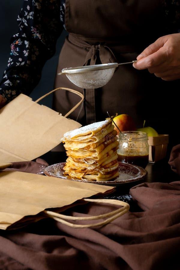 苹果煎饼包手工艺盒递送,甜点黑色背景手食 免版税库存照片
