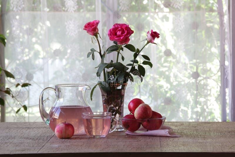 从苹果的蜜饯在一个透明水罐和玫瑰花束  免版税图库摄影