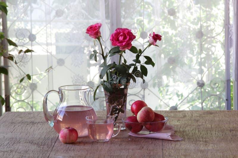 从苹果的蜜饯在一个透明水罐和玫瑰花束  图库摄影
