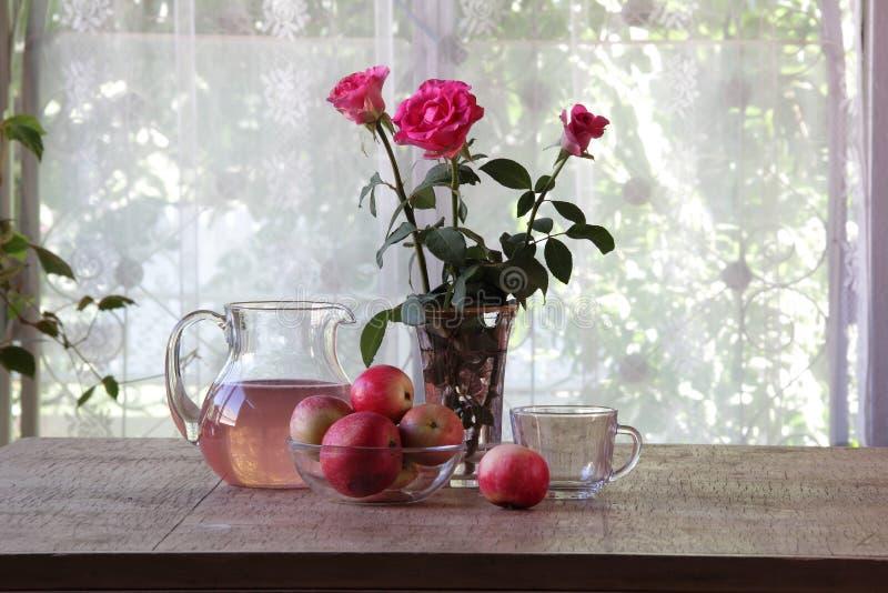 从苹果的蜜饯在一张木桌上的一个透明水罐 免版税图库摄影