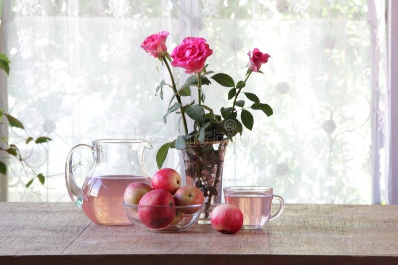 从苹果的蜜饯在一张木桌上的一个透明水罐 免版税库存照片