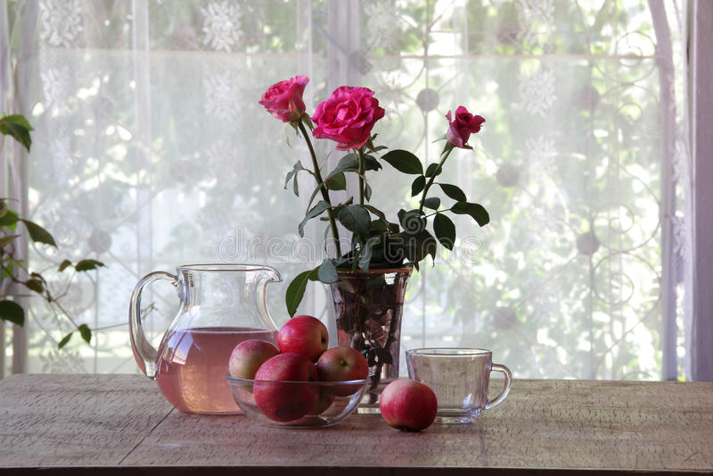 从苹果的蜜饯在一张木桌上的一个透明水罐 库存图片