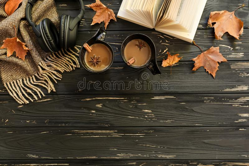 苹果秋天对光检查袋装花瓶的构成干燥叶子 两杯咖啡,糖,围巾,耳机,开放书,槭树在黑木背景离开 库存照片