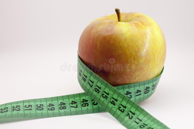苹果背景饮食绿色查出在微笑的磁带白人妇女 库存图片