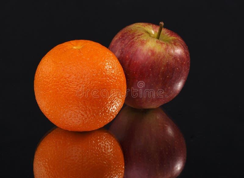 苹果背景黑色桔子 免版税库存图片