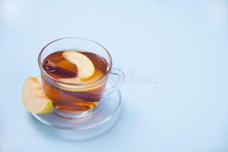 苹果茶饮料用肉桂条、八角和丁香 在杯子的季节性拳打在蓝色背景 免版税库存图片