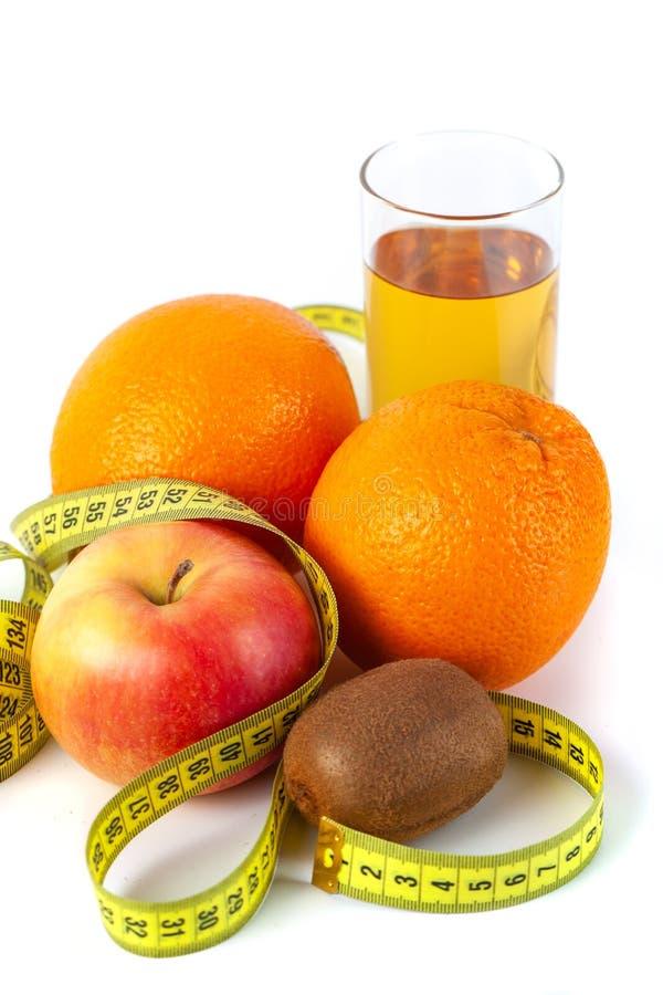 苹果计算机、桔子、猕猴桃和苹果汁与卷尺在白色背景 免版税库存照片