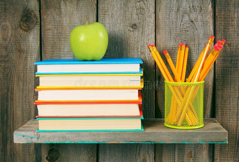 苹果计算机、铅笔和书在一个木架子 免版税库存图片