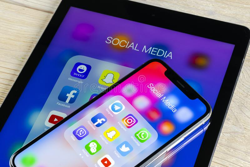 苹果计算机与社会媒介facebook, instagram,慌张,在屏幕上的snapchat应用象的iPhone x和iPad  社会媒介象 库存图片