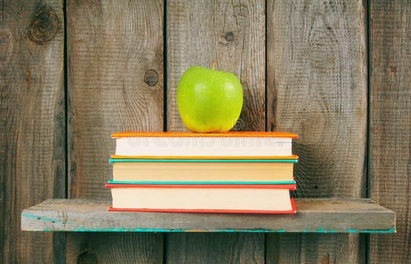 苹果计算机和书在一个木架子 库存照片