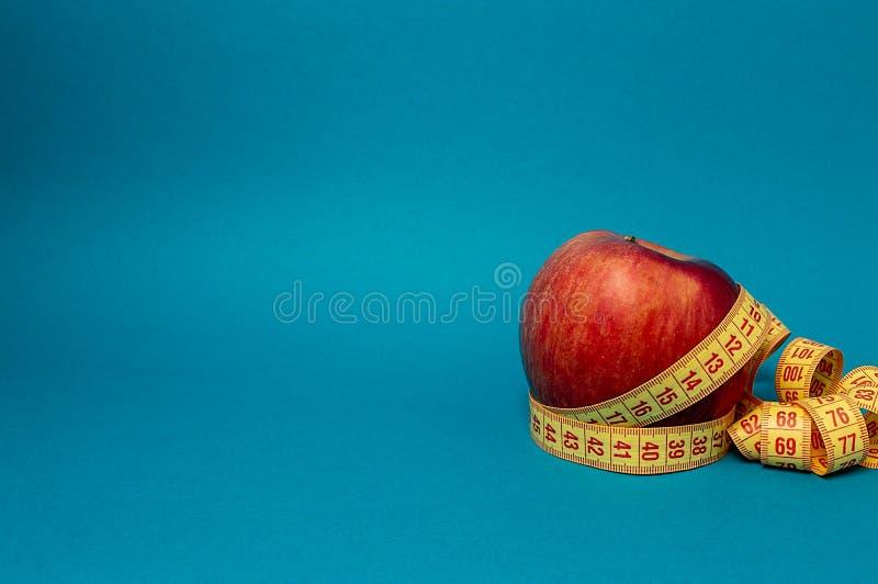 苹果计算机和卷尺亭亭玉立的健身饮食体育生活 库存照片