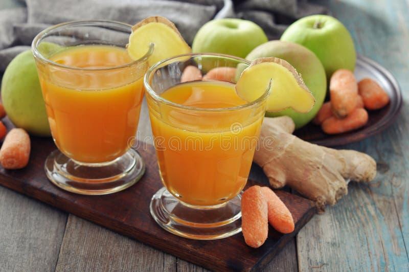 苹果计算机和红萝卜汁用姜 免版税库存照片