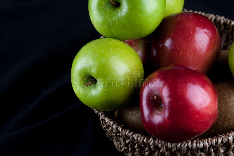 苹果计算机在黑背景的水果篮 库存图片