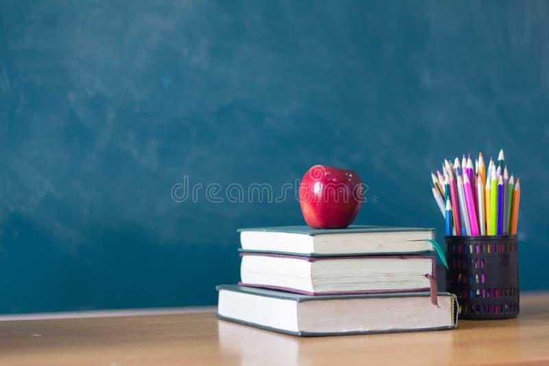 苹果计算机投入学习的书,背景是黑板, edu 库存照片