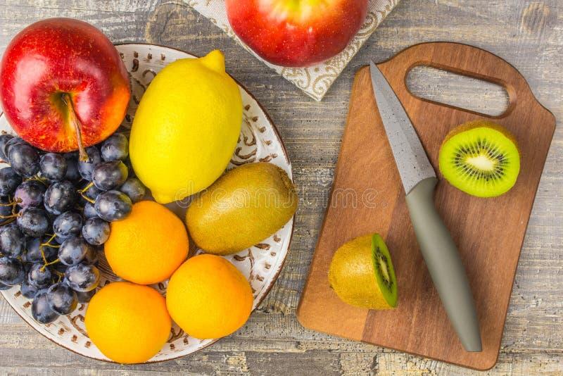 苹果计算机桔子、柠檬、果子、猕猴桃、板材和木板 刀子在桌上的葡萄背景 免版税库存图片