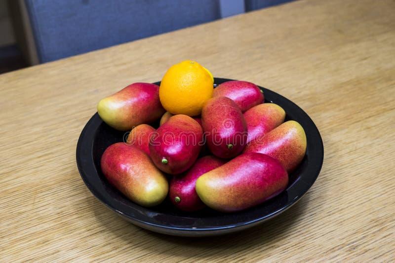 苹果计算机芒果、桔子和柠檬在碗在厨房里 库存图片