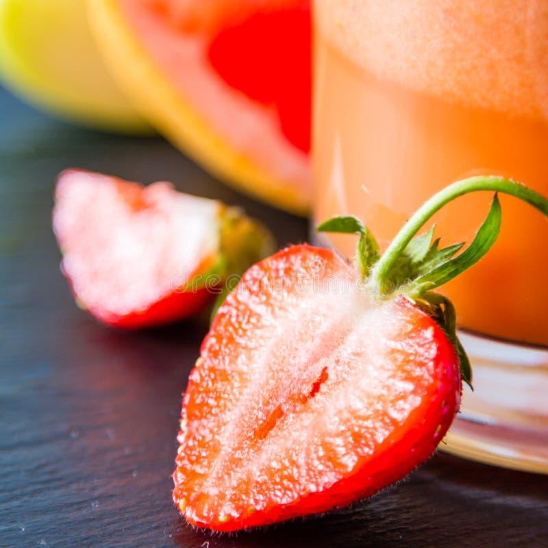 苹果计算机葡萄柚和草莓圆滑的人成份 免版税图库摄影