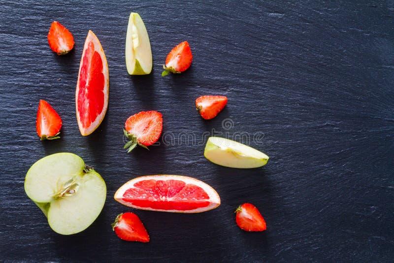 苹果计算机葡萄柚和草莓圆滑的人成份 库存照片