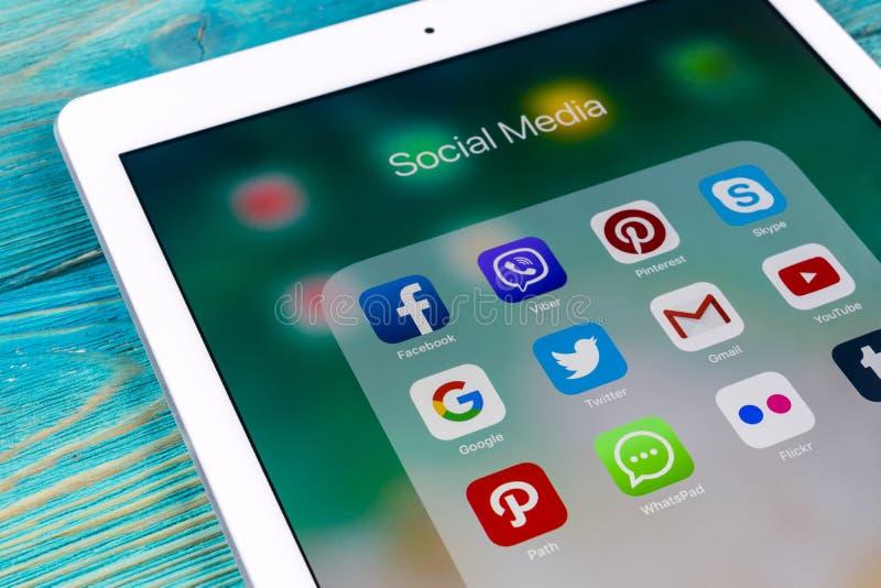 苹果计算机iPad赞成在与社会媒介facebook, instagram,慌张,在屏幕上的snapchat应用象的木桌上  片剂 图库摄影