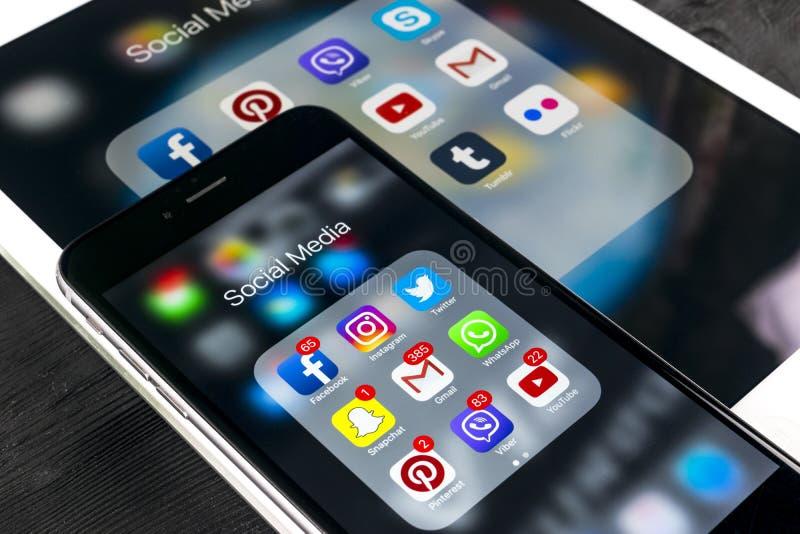 苹果计算机iPhone 7和iPad赞成与社会媒介facebook, instagram,慌张,在屏幕上的snapchat应用象  智能手机 库存图片