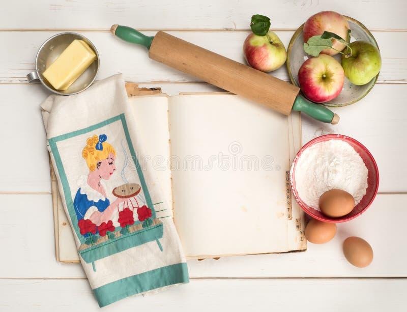 苹果饼与空白的食谱书页,滚针,葡萄酒洗碗布,在困厄的白色的蛋黄草类的烘烤成份 免版税库存照片