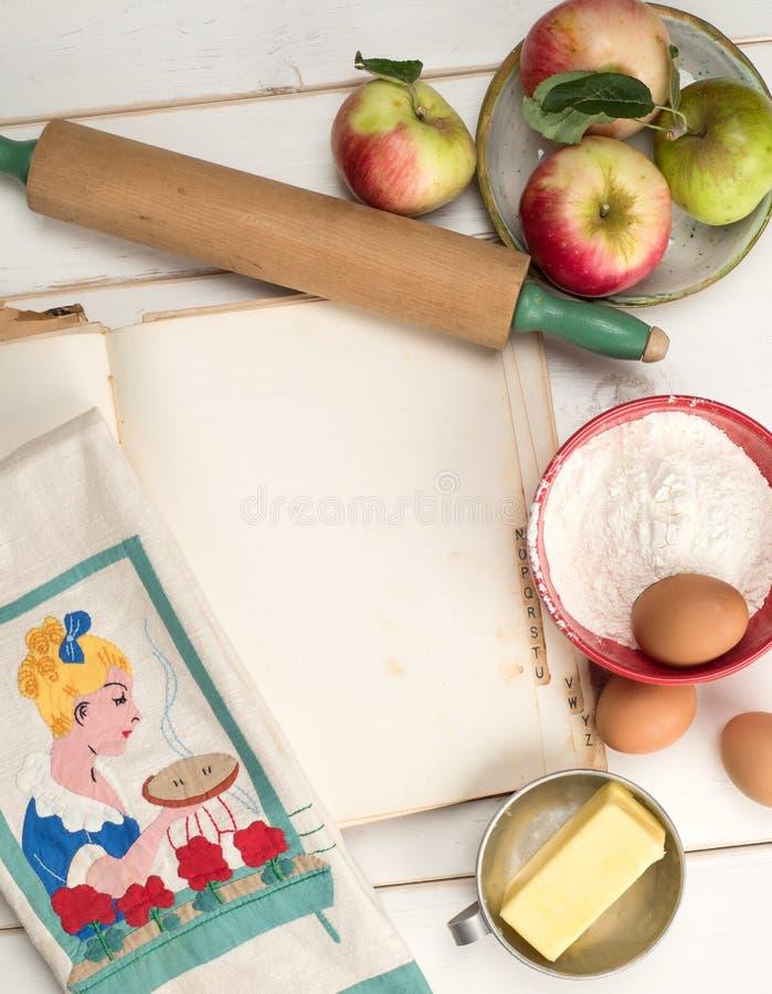 苹果饼与空白的食谱书页,滚针,葡萄酒洗碗布,在困厄的白色的蛋黄草类的烘烤成份 免版税库存图片