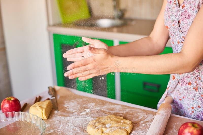 苹果饼的妇女揉的面团在厨房用桌上 与面粉一起使用 r 免版税图库摄影