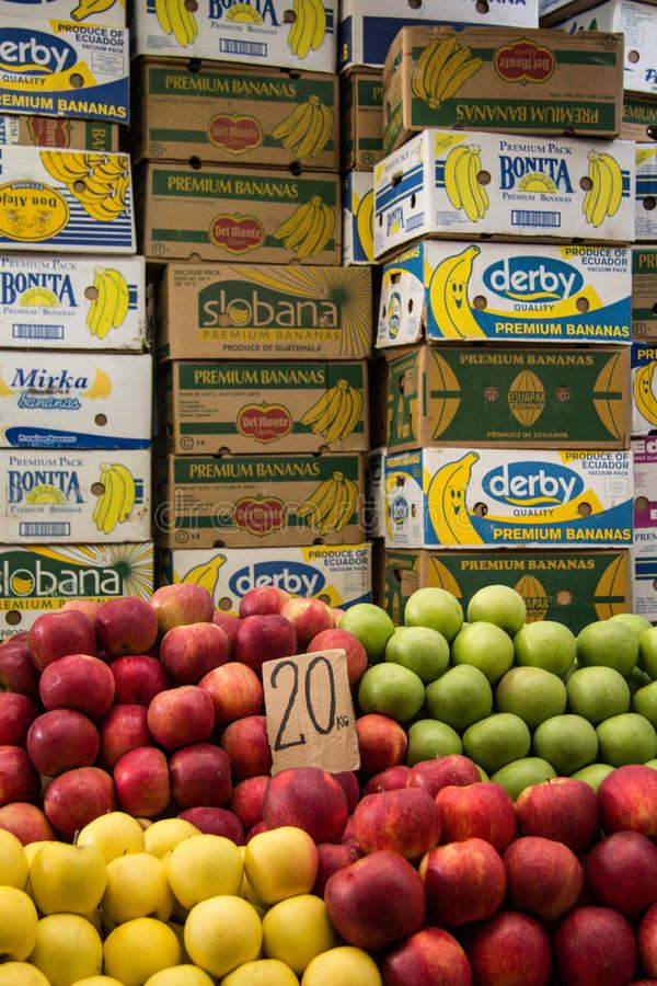 苹果,黄色,红色和绿色,待售在斯科普里义卖市场,在充分纸板箱其他果子前面 免版税库存图片