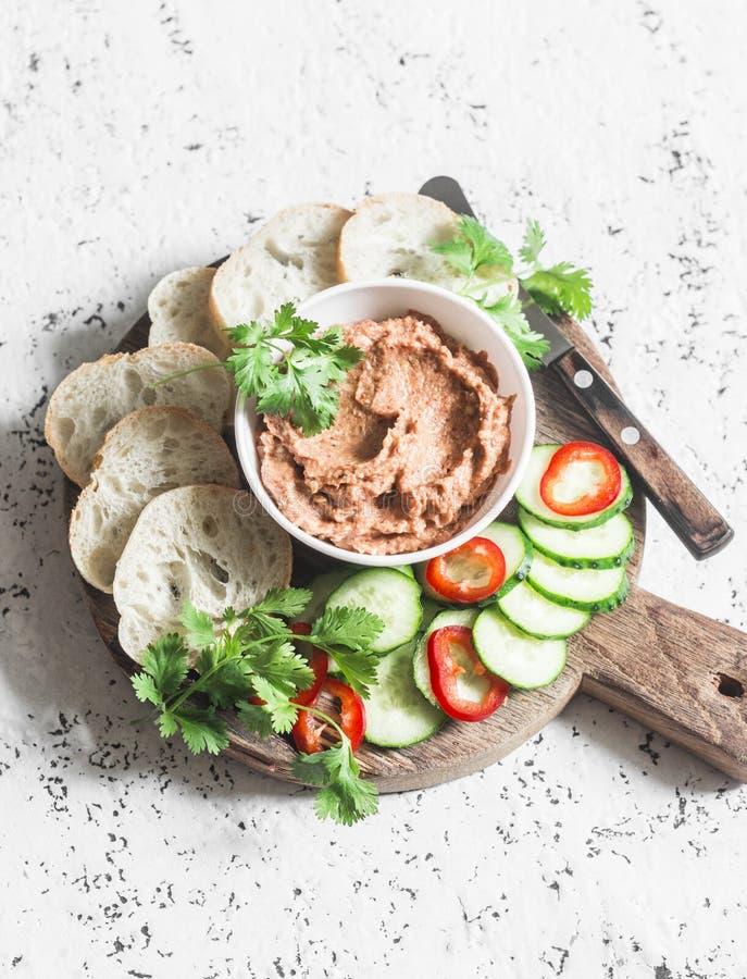 茄子,熏制的辣椒粉,核桃浸洗,菜和面包在木切板在轻的背景 免版税库存图片