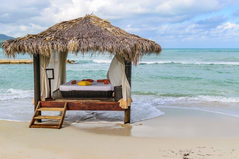 茅草屋顶屋顶小屋在热带海岛白色沙滩的按摩床 免版税图库摄影